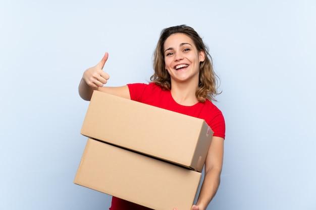 Jonge blondevrouw die een doos houden om het naar een andere plaats met omhoog duim te verplaatsen