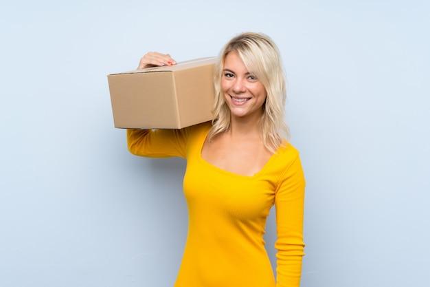 Jonge blondevrouw die een doos houden om het naar een andere plaats te verplaatsen