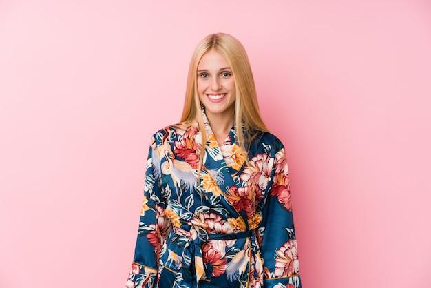 Jonge blondevrouw die een gelukkig, glimlachende en vrolijke kimonopyjama dragen.