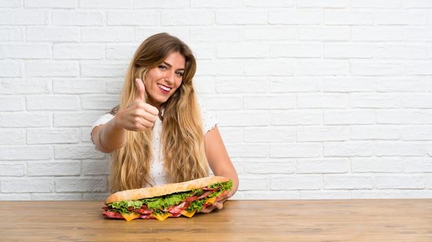 Jonge blondevrouw die een grote sandwich met omhoog duim houden
