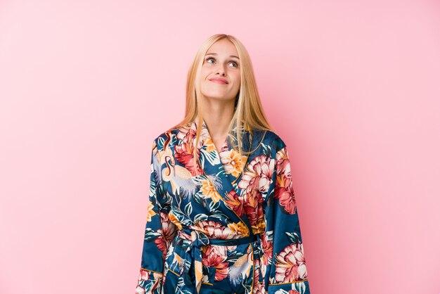 Jonge blondevrouw die een kimonopyjama dragen die dromen van het bereiken van doelen en doeleinden