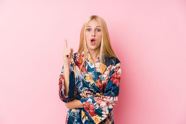 Jonge blondevrouw die een kimonopyjama dragen die één of ander groot idee, concept creativiteit hebben.