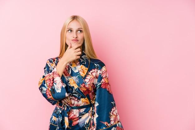 Jonge blondevrouw die een kimonopyjama dragen die zijdelings met twijfelachtige en sceptische uitdrukking kijken.