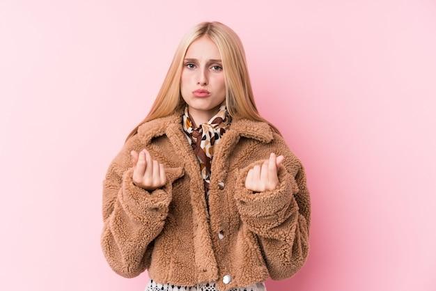 Jonge blondevrouw die een laag dragen tegen een roze muur die aantoont dat zij geen geld heeft.