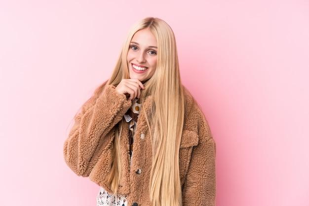 Jonge blondevrouw die een laag dragen tegen een roze muur die gelukkig en zeker, wat betreft kin met hand glimlachen.