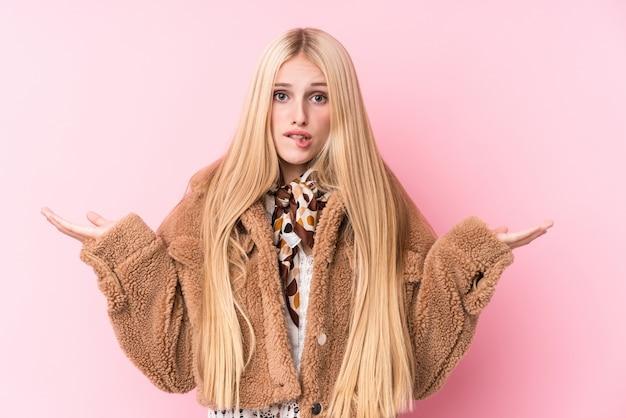 Jonge blondevrouw die een laag dragen tegen een roze muur verwarde en twijfelachtige schouders ophalen om een exemplaarruimte te houden.