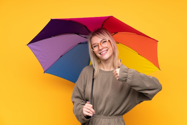 Jonge blondevrouw die een paraplu over het geïsoleerde gele muur geven houden duimen op gebaar