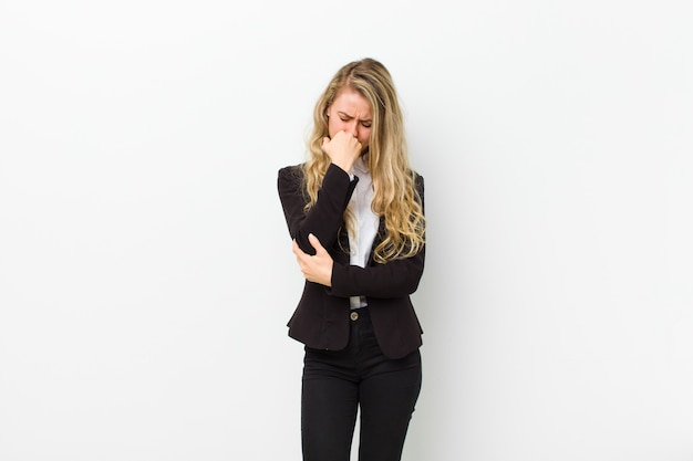 Jonge blondevrouw die ernstig, nadenkend en bezorgd voelen, zijdelings starend met hand gedrukt op kin op witte muur