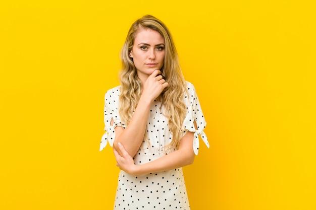 Jonge blondevrouw die ernstig, verward, onzeker en nadenkend kijken, twijfelend onder opties of keuzen over gele muur