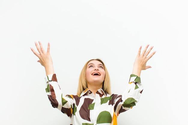 Jonge blondevrouw die gelukkig, verbaasd, gelukkig en verrast voelen, vierend overwinning met beide handen omhoog in de lucht tegen witte muur