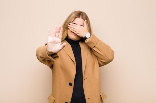 Jonge blondevrouw die gezicht behandelen met hand en andere hand vooraan zetten om camera tegen te houden, die foto's of beelden weigeren