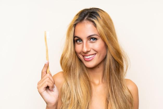 Jonge blondevrouw die haar tanden borstelt