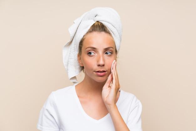 Jonge blondevrouw die make-up verwijderen uit haar gezicht met katoenen stootkussen
