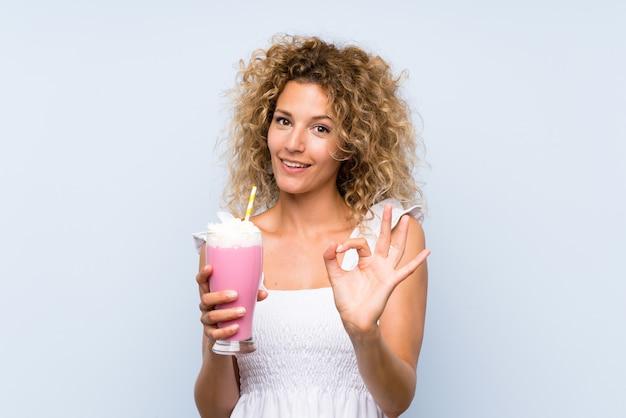 Jonge blondevrouw die met krullend haar een aardbeimilkshake houden die ok teken met vingers tonen
