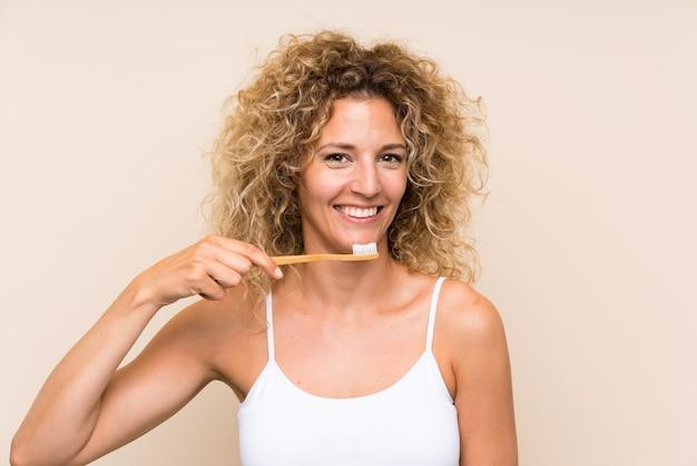 Jonge blondevrouw die met krullend haar haar tanden borstelt