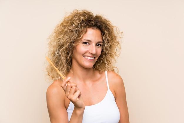 Jonge blondevrouw die met krullend haar haar tanden poetsen