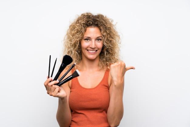 Jonge blondevrouw die met krullend haar heel wat make-upborstel houden richtend aan de kant om een product te presenteren