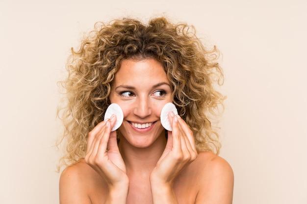 Jonge blondevrouw die met krullend haar make-up verwijderen uit haar gezicht met katoenen stootkussen