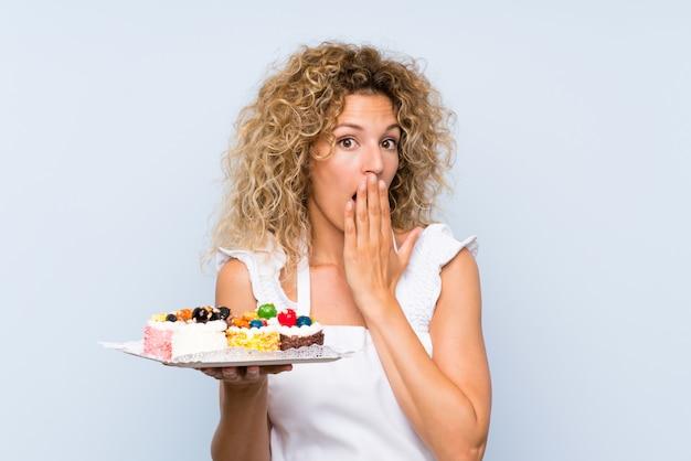 Jonge blondevrouw die met krullend haar veel verschillende minicakes met verrassingsgelaatsuitdrukking houden