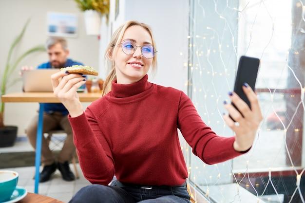 Jonge blondevrouw die met sandwich selfie terwijl het zitten in koffie in vrije tijd maken