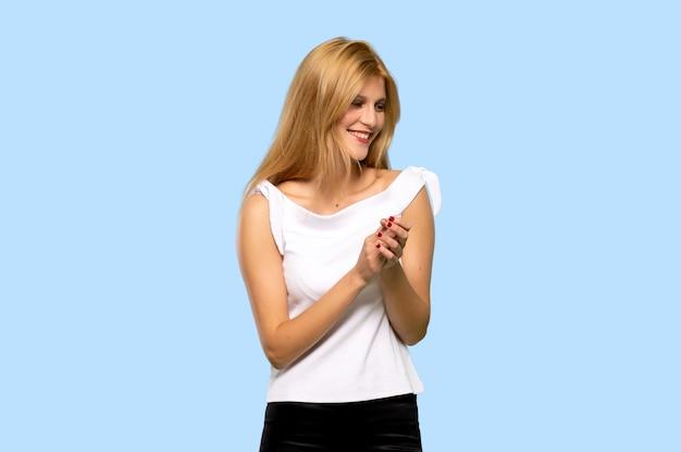 Jonge blondevrouw die na presentatie in een conferentie over geïsoleerde blauwe achtergrond toejuichen