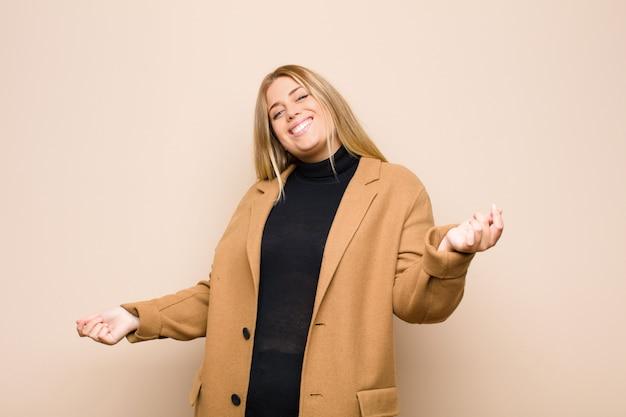 Jonge blondevrouw die, onbezorgd, ontspannen en gelukkig, het dansen en het luisteren aan muziek glimlachen, die pret hebben bij een partij tegen vlakke muur