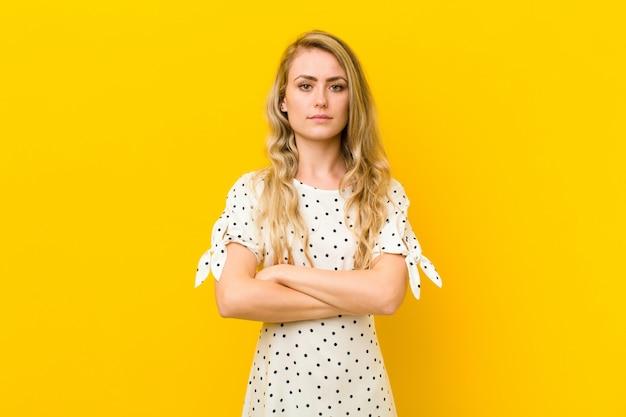 Jonge blondevrouw die ontevreden en teleurgesteld voelen, kijkend ernstig, geërgerd en boos met gekruiste wapens tegen gele muur