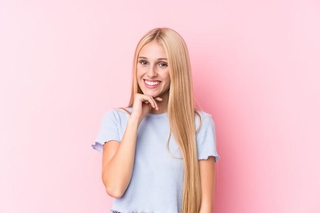 Jonge blondevrouw die op roze muur gelukkig en zeker glimlachen, wat betreft kin met hand.