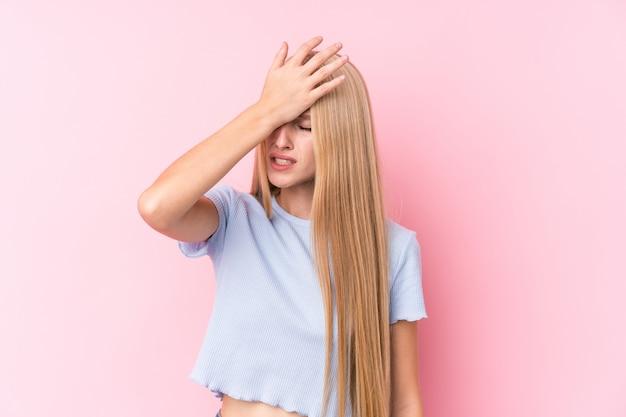 Jonge blondevrouw die op roze muur iets vergeten, voorhoofd met palm meppen en ogen sluiten.