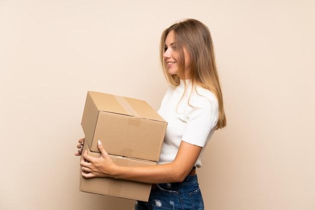 Jonge blondevrouw die over geïsoleerde muur een doos houden om het naar een andere plaats te verplaatsen