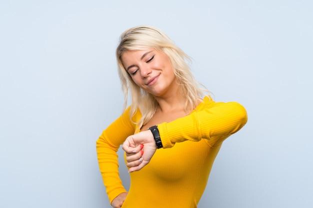 Jonge blondevrouw die over geïsoleerde muur het polshorloge kijken