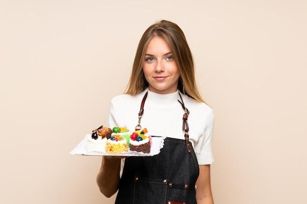Jonge blondevrouw die over geïsoleerde muur minicakes houden