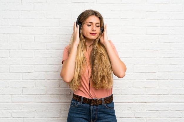Jonge blondevrouw die over witte bakstenen muur aan muziek met hoofdtelefoons luisteren