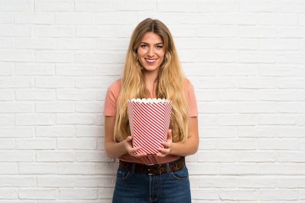 Jonge blondevrouw die over witte bakstenen muur een kom popcorns houden