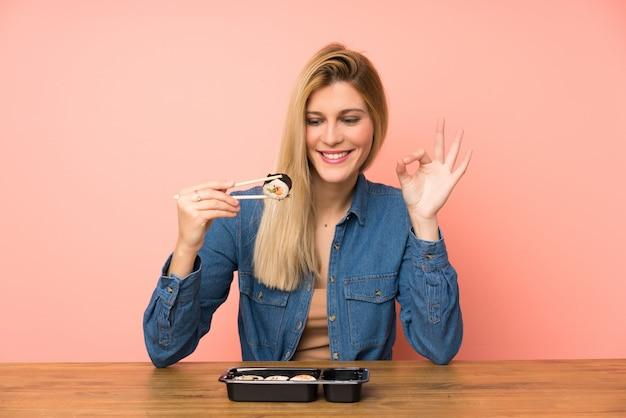 Jonge blondevrouw die sushi eten