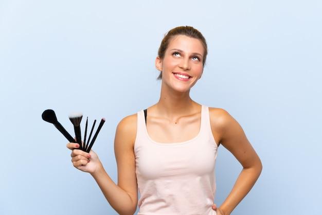 Jonge blondevrouw die veel make-upborstel houden omhoog kijkend terwijl het glimlachen