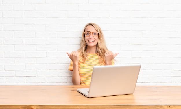 Jonge blondevrouw die vreugdevol glimlachen en gelukkig kijken, die onbezorgd en positief met beide duimen voelen die omhoog laptop gebruiken