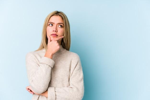 Jonge blondevrouw die zijdelings met twijfelachtige en sceptische uitdrukking kijken