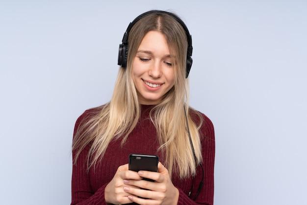 Jonge blondevrouw het luisteren muziek en het kijken aan mobiel