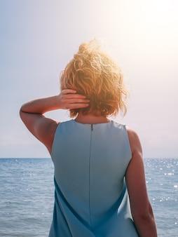 Jonge blondevrouw in de zomer blauwe kleding die zich op strand bevinden en aan het overzees kijken