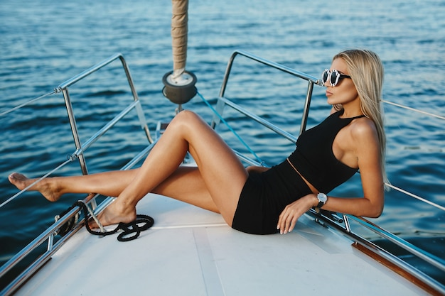 Jonge blondevrouw in het korte zwarte kleding stellen op een jachtschip
