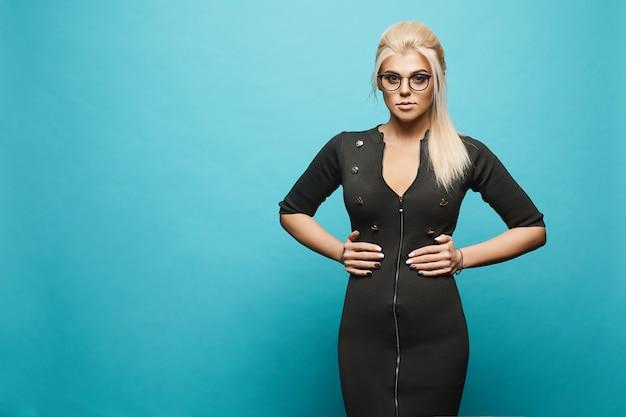 Jonge blondevrouw in kleding met ritssluiting en in eyewear bij blauwe muur