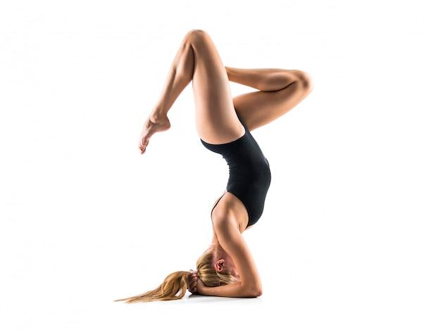 Jonge blondevrouw in maillot die ritmische gymnastiek uitoefent
