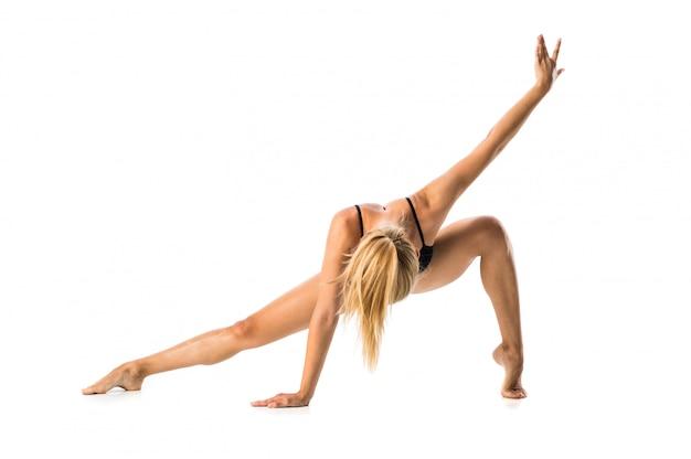 Jonge blondevrouw in maillot het praktizeren yogales
