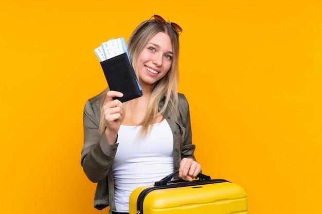 Jonge blondevrouw in vakantie met koffer en paspoort
