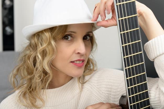 Jonge blondevrouw met de akoestische gitaar