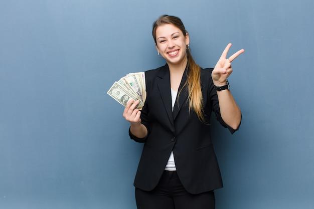 Jonge blondevrouw met dollarbankbiljetten over de muur van de grungemuur