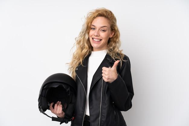 Jonge blondevrouw met een motorhelm die op witte muur met omhoog duimen wordt geïsoleerd omdat er iets goeds is gebeurd