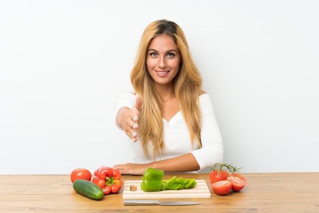 Jonge blondevrouw met groenten in een lijsthandenschudden na goede deal