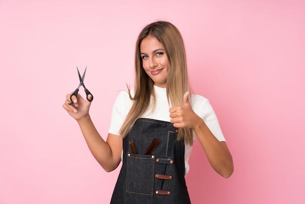Jonge blondevrouw met kapper of kapperskleding met omhoog duim
